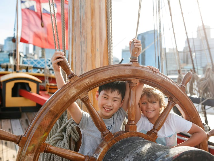 Kids at the wheel of the ship Endeavour