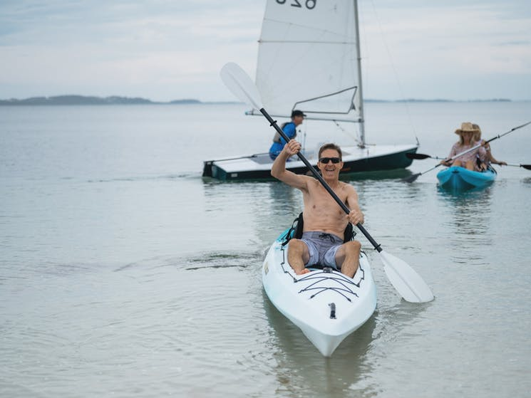 Man smiling from his kayak, two women kayaking together behind him and a sail boat in the background