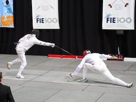 Two fencers in motion during the finals