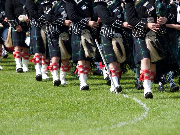 Image of pipers in Scottish dress , marching and playing bagpipes