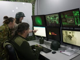 Three people dressed in army gear looking at six monitors