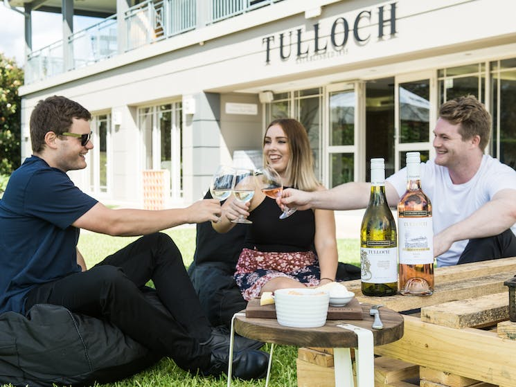 A small group relaxing outdoors at the Tulloch Cellar Door