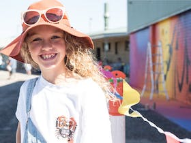 Curly haired girl in front of George Rose Mural 2018