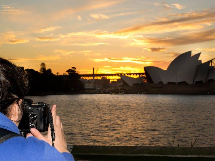 Sunset behind Opera House as photorapher takes photo