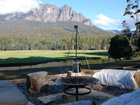 Mt Roland in back ground of fire pit with billy on fire brewing tea