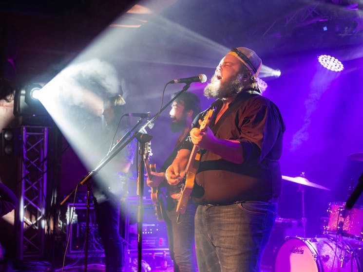 Brad Cox singing at microphone with purple lights