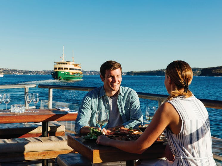 Couple enjoying food and drinks at Hugos Manly, at Manly Wharf