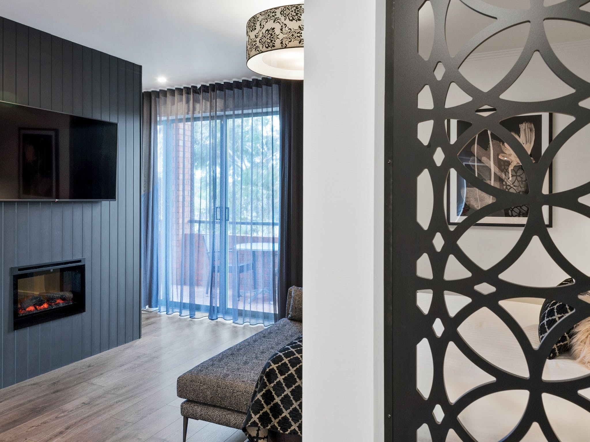 Looking through entry to bedroom with fireplace and television, looking out to balcony