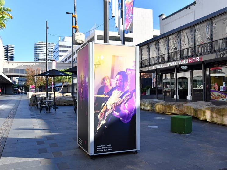 A large scale photograph of a singer is on exhibit in an outdoor mall.