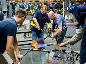 Brian Corr shapes his glass vessel with a team of assistants.