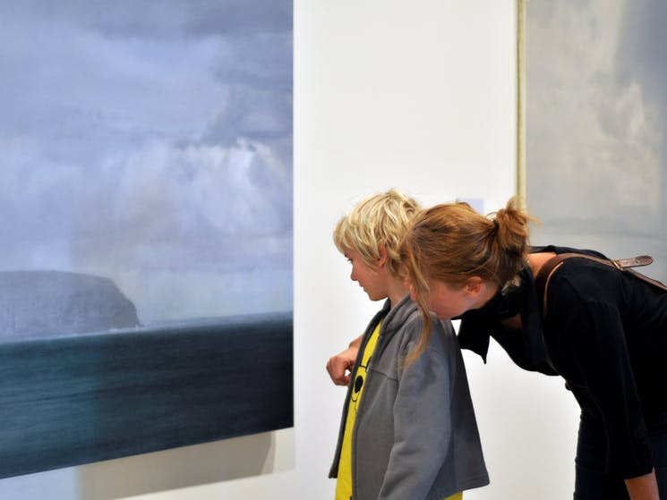 Patrons viewing a painting in the gallery