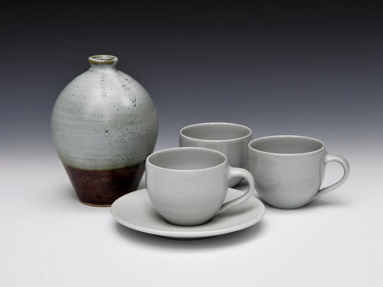 A round bottle in brown and grey with classic shaped very simple cups and saucers.
