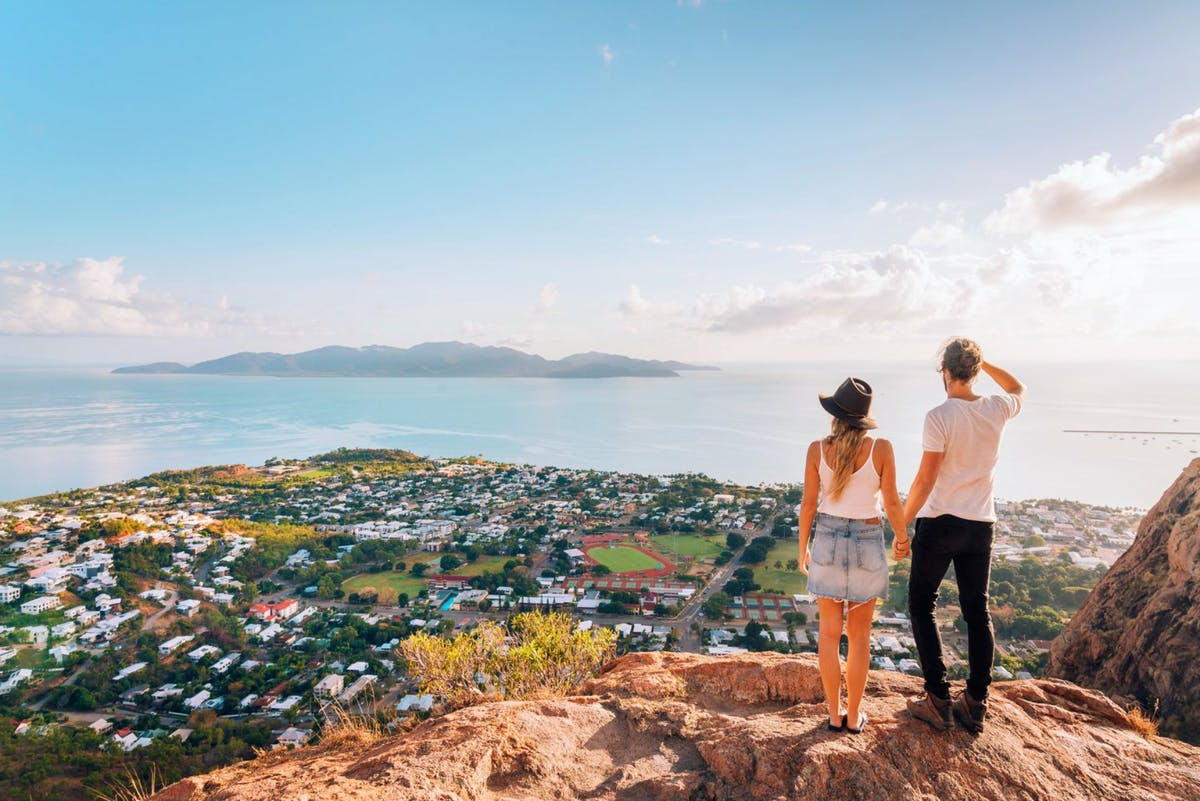 Two people on a hill looking out over a body of water