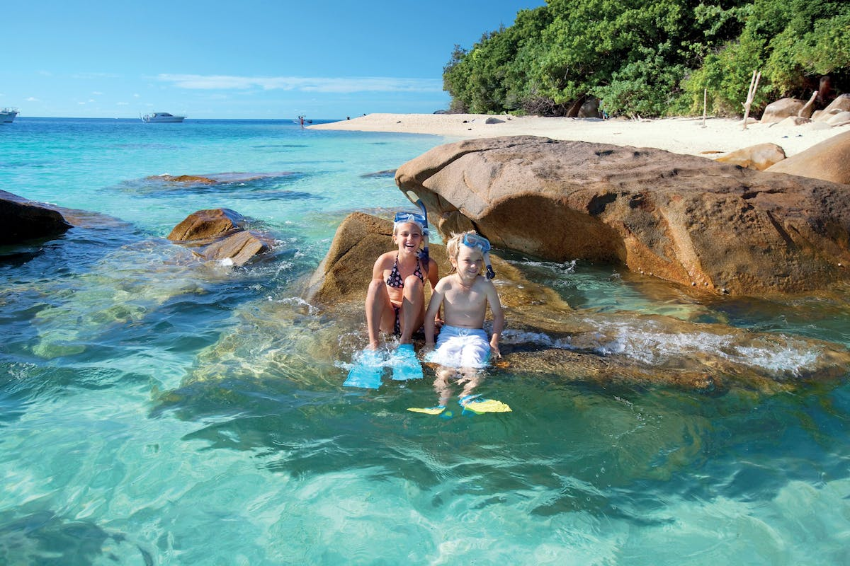 Children in snorkelling gear on boulder at beach at Fitzroy Island
