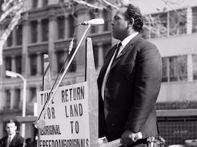 A black and white photograph of Indigenous rights activist Ray Peckham standing at a podium