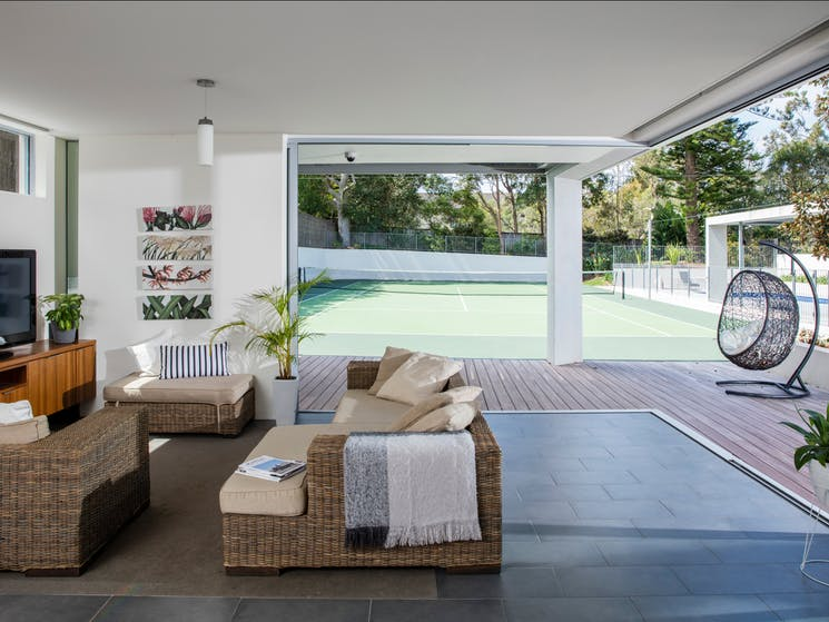 Living room open to tennis court and pool