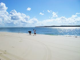Two people line fishing at waters edge on sandy beach with blue skies overhead.