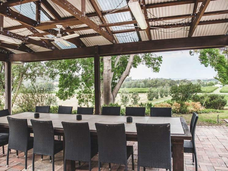 Outdoor dining area includes fire pit, wood fired pizza oven and barbecue