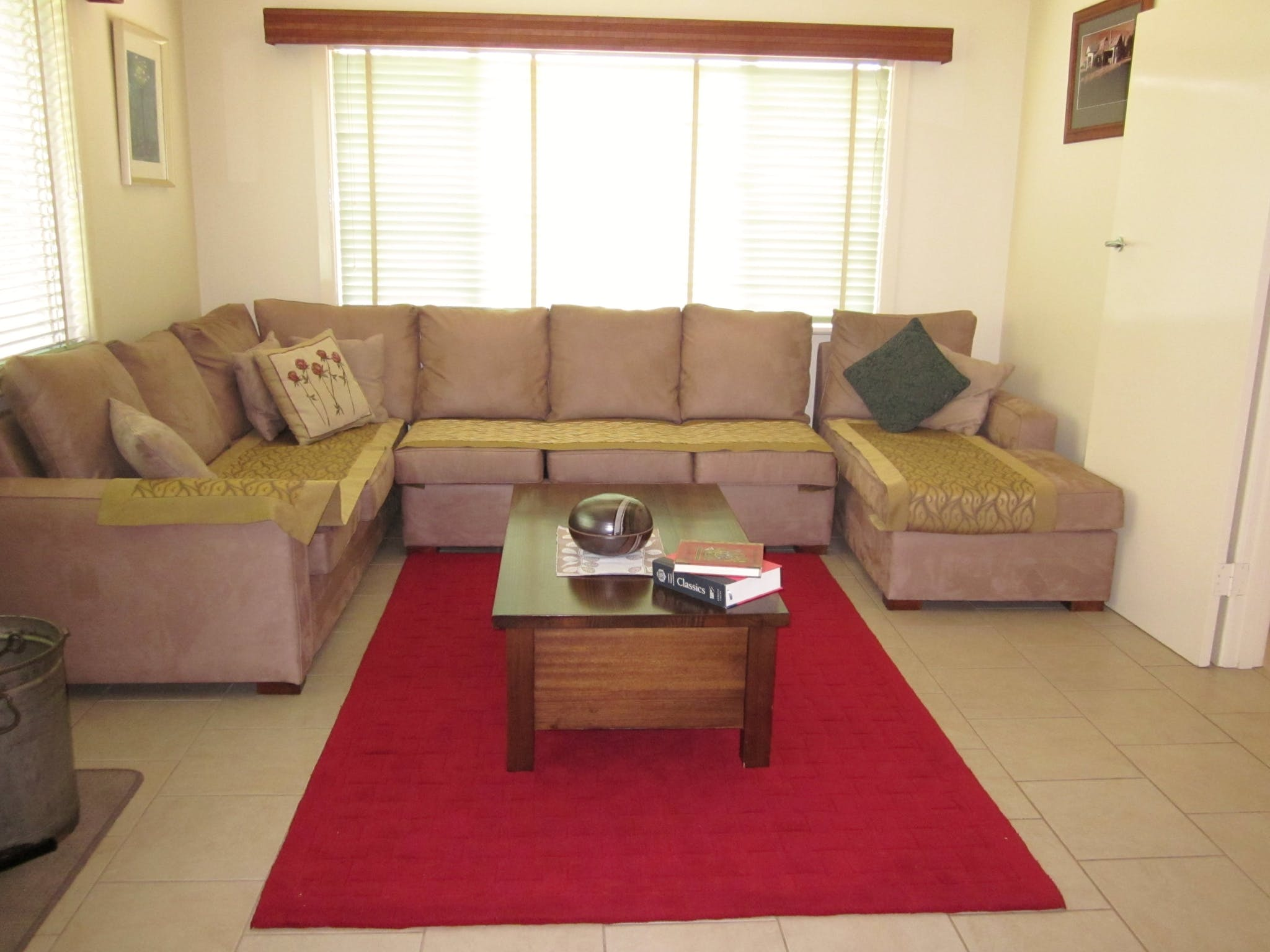 Lounge room with corner lounge suite and wood heater.