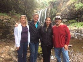 people standing near waterfall