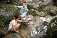Aboriginal guide at Mossman Gorge with guests, demonstrating ochre paints by the creek.