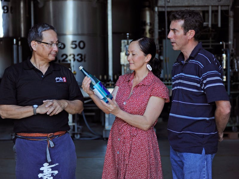 Owner of Sake brewery showing a couple a bottle of Sake