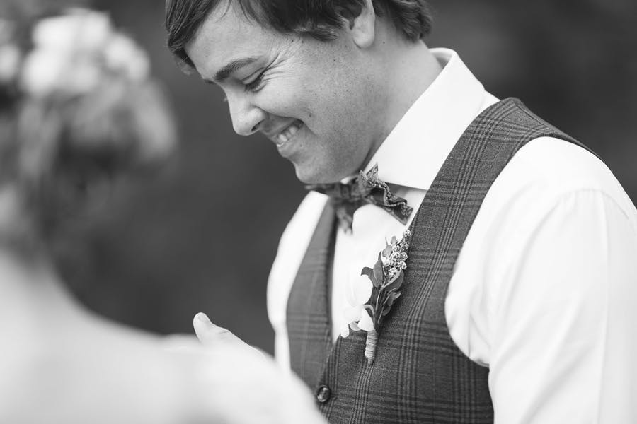 A happy groom smiles during his wedding ceremony