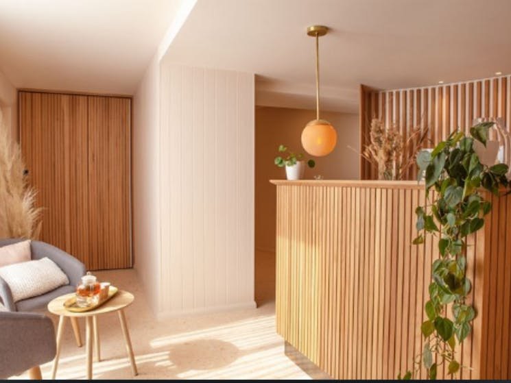 Interior shot of spa, with wooden welcome desk and seating area.