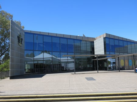 Exterior of Wagga Wagga City Library, blue sky and glass window covered building