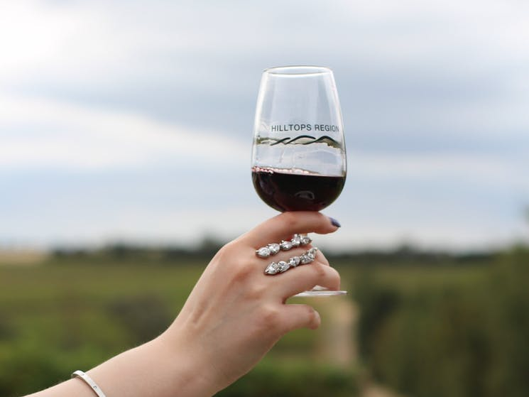 Hand holding glass of red wine with Hilltops Region logo