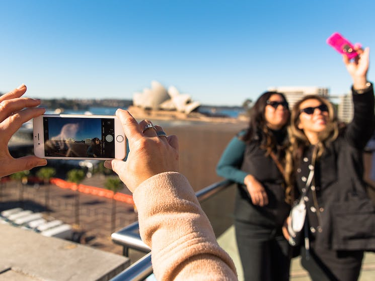 Two women doing a selfie with Opera House in background