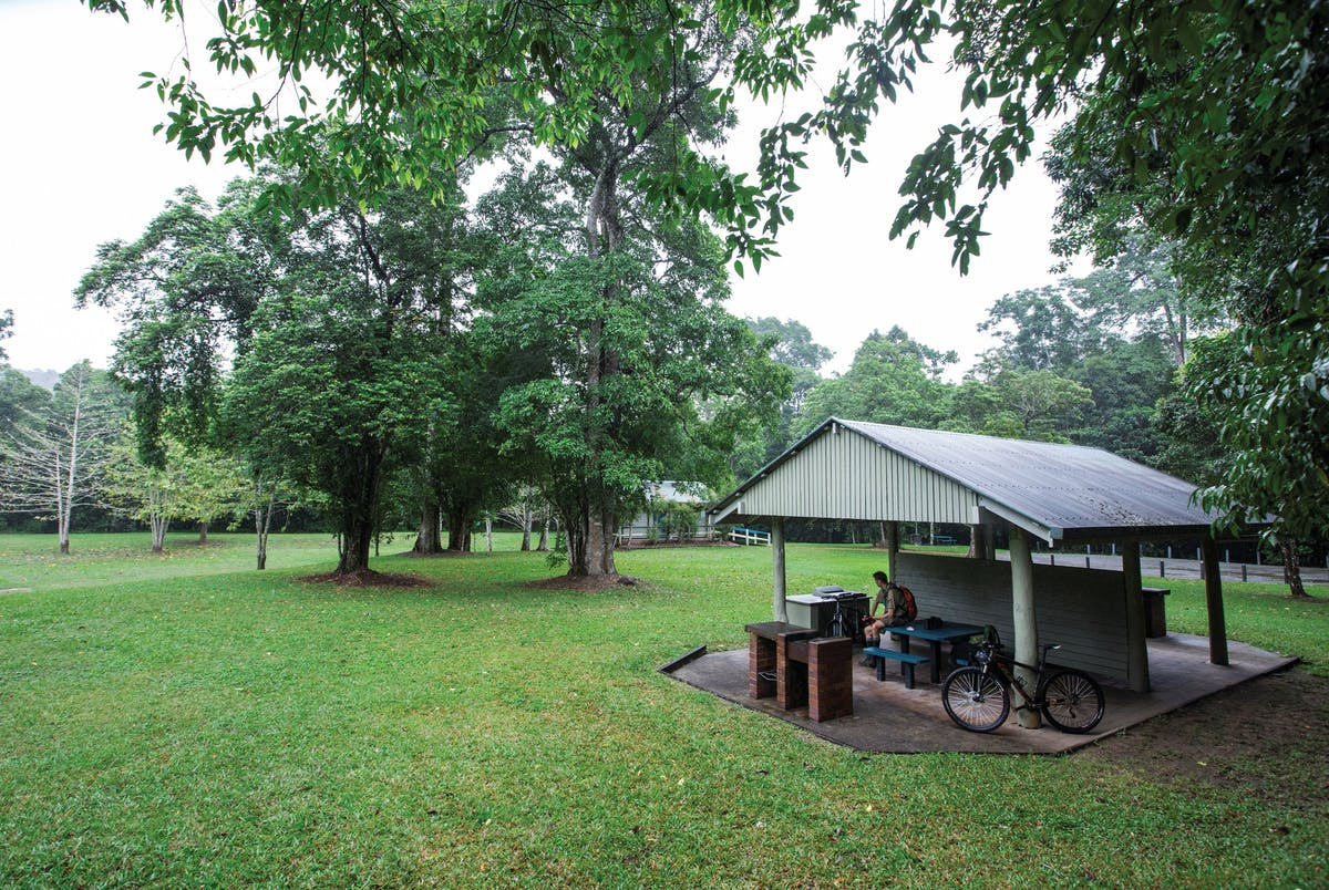 Walker and bike sitting in shelter shed in picnic area.