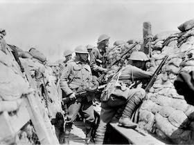 Unidentified members of the 2nd Australian Division in the trenches in the Bois Grenier sector. The soldier in the forground is looking through a periscope; the man to his left is holding a Lewis gun.