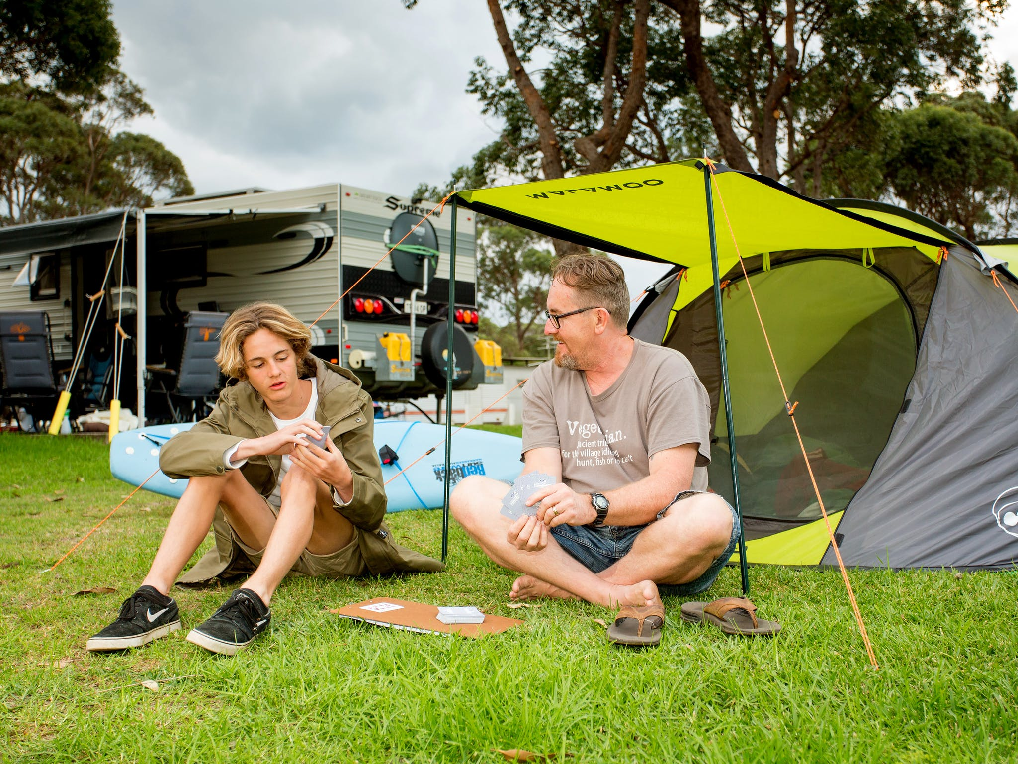 Dad and son playing cards on lovely green grass  in front of their tent, caravans in the background