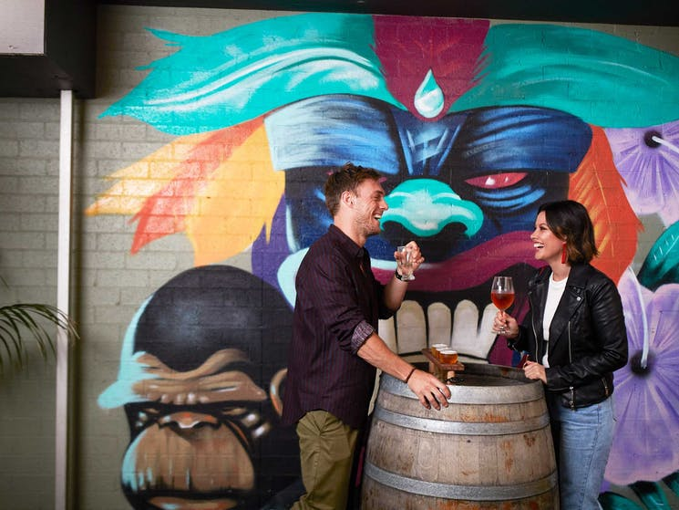Couple drinking in front of mural