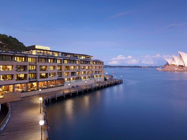 Hero landscape shot of Park Hyatt Sydney hotel under Harbour Bridge and across from the Opera House