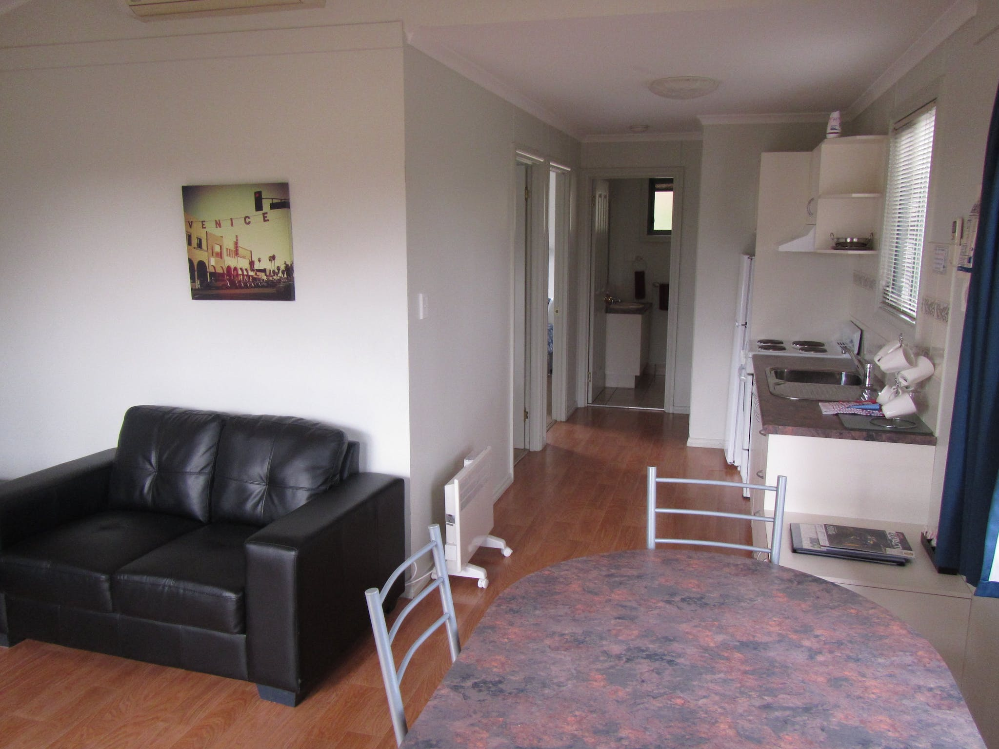 Two bedroom deluxe cabin, showing kitchen and dining area through to bathroom
