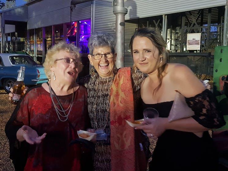 Three women at an outdoor party in Cobar enjoying a laugh