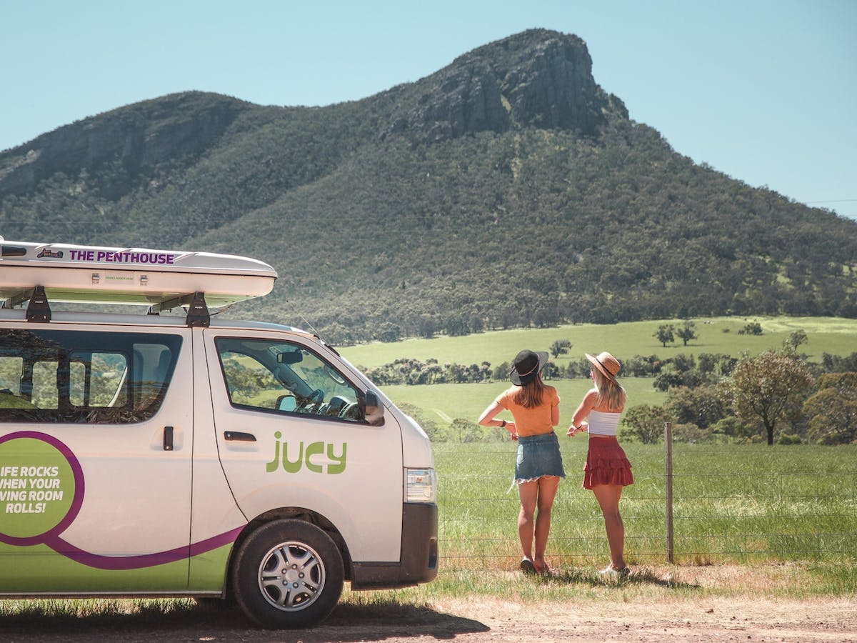 Two girls and campervan overlooking mountain