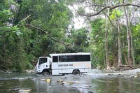 Custom built Cooktown 4WD coach driving across creek crossing.
