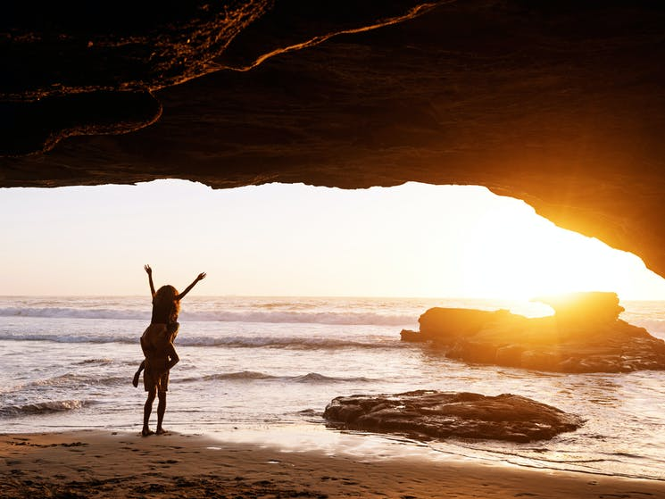 A couple embracing the sunrise inside a beach cave