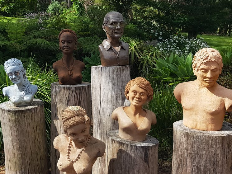 Six clay sculptures of heads and torsos sitting on large tree stumps