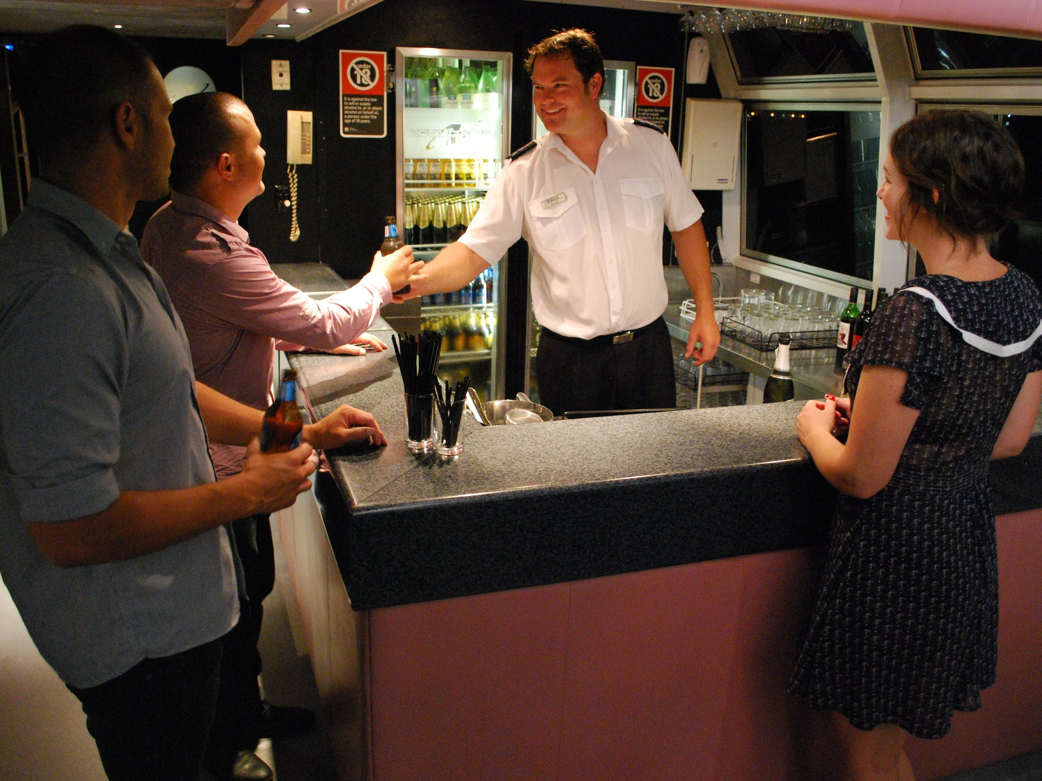 Peter serving drinks to patrons at the bar on 'The Princess'