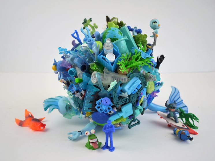 A blue merman lies on the ground covered in blue toys like coral