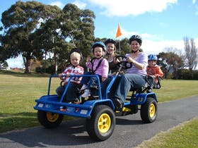 A family riding on a pedal buggie