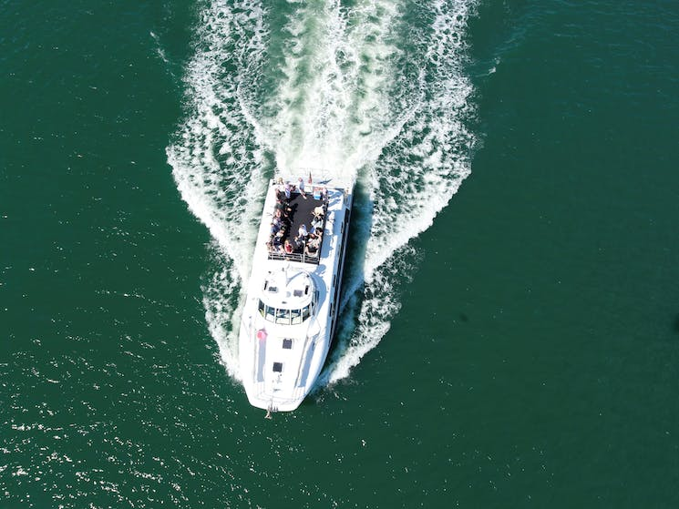 Picture looking down on vessel 'Bay Connections' cruising on the water in Newcastle Harbour
