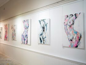 White gallery wall with 6 large canvases of nude women painted in a colourful abstract style.