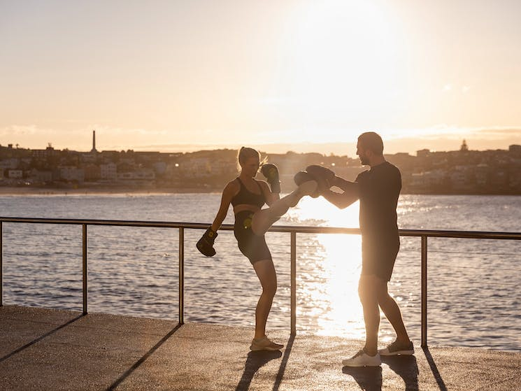 Woman working out with a personal trainer at Bondi Beach, Sydney