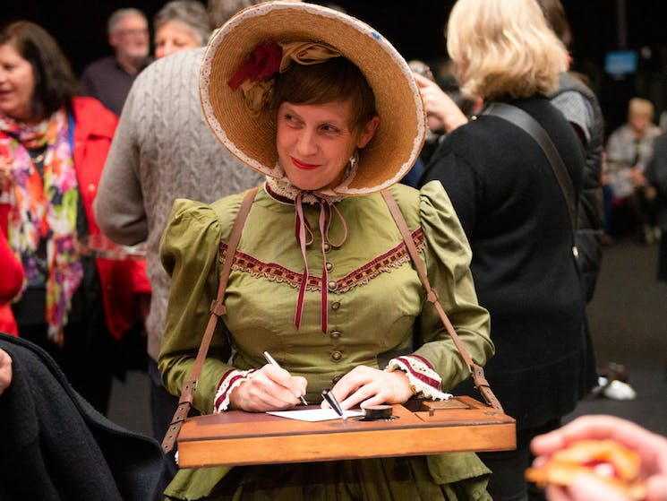 Poet in nineteenth century dress and bonnet with portable writign table