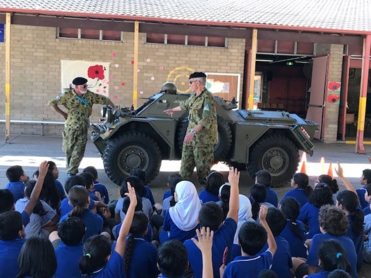 Museum volunteers show a Ferret Scout Car to young school students and answer their many questions